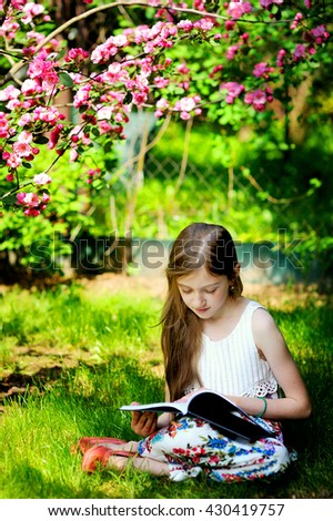 Adorable kid girl in blooming apple garden on beautiful spring day reading book