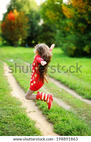 Adorable kid girl in red sweater dress and stripe rainboots jumping and having fun outdoors in the sunny autumn day