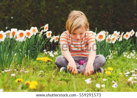 Adorable little blond boy playing with colorful easter eggs in the park, egg hunt