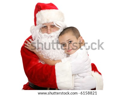 Adorable little boy giving Santa Claus a hug.  Isolated on white.