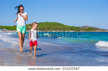 Adorable little girl and happy mom during tropical vacation