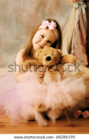 Adorable little girl dressed as a ballerina in a tutu, hugging a teddy bear next to pink roses.
