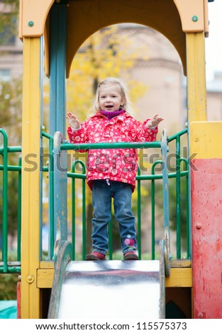 Adorable little girl having fun on the playground