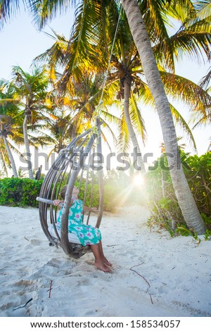 Adorable little girl in a dress and sunglasses on swing at white sandy Caribbean beach