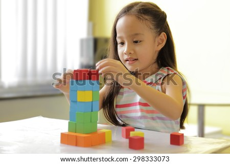 Adorable little girl playing toy blocks in a bright room - copy space on upper-left portion