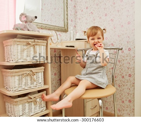 Adorable little girl playing with mommy's make up about make up table