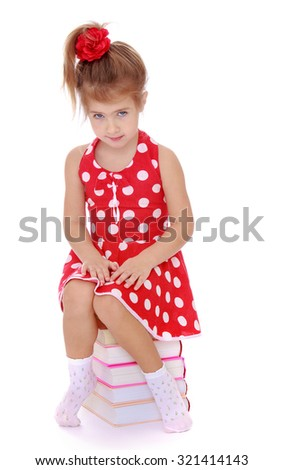 Adorable little girl sitting on books. The girl is dressed in a summer red dress with polka dots-Isolated on white background