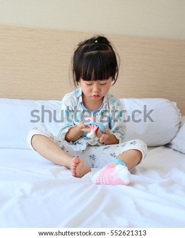 Adorable little girl trying to put a socks on the bed.