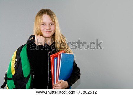 Adorable little girl with backpack and books