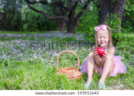 Adorable little girl with big red apple in blossoming orchard