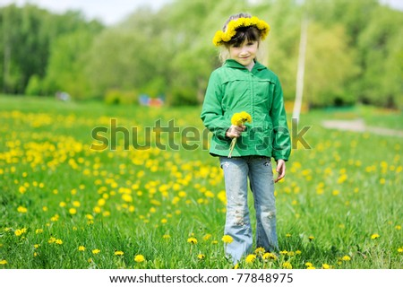 Adorable little girl with long dark hair and dandelions wreath on yellow dandelions field