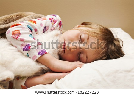 Adorable little girl with toy sleeping
