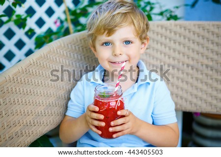 Adorable little kid boy drinking healthy fruits and vegetables juice smoothie in summer. Happy child enjoying organic drink.