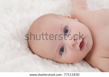 Adorable naked baby boy with blue eyes, lying on  soft fur blanket, smiling