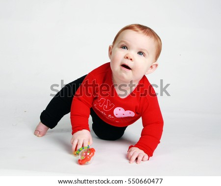 Adorable red haired baby learning to crawl and set against a white background.