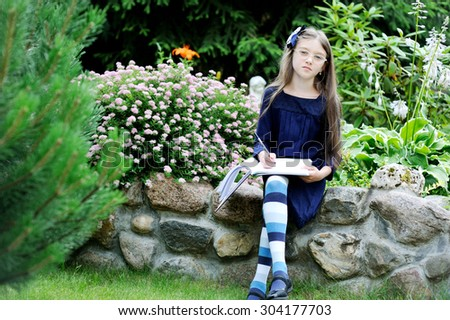 Adorable school aged kid girl in blue uniform dress outdoor