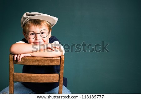 Adorable school boy with chalkboard copy space