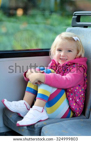 Adorable smiling girl riding bus sitting comfortable on passenger seat nearby the window. Portrait of smiling child on bus seat. Independent little kid travelling in urban environment.