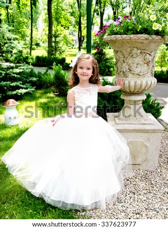 Adorable smiling little girl in princess dress outdoor