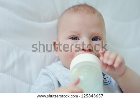 Adorable three month baby holding bottle and drinking milk