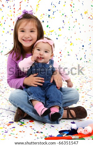 Adorable 5 year and 4 month old sisters over paint splattered background.