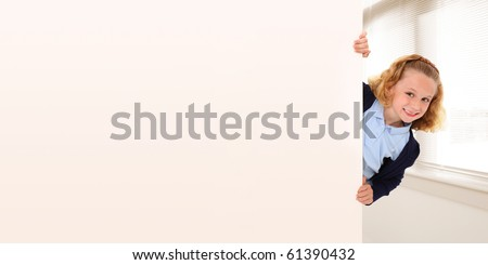 Adorable 7 year old girl in school uniform peeking out behind wall. Space for copy.