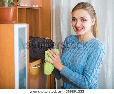 Aduiltl girl in blue jersey dusting shelves at home