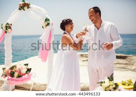 Adult bride and groom cross their hands to drink champagne by the sea