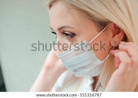 adult dentist puts a protective mask on her mouth