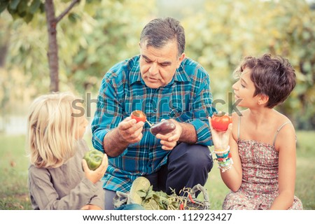 Adult Farmer with Children and Harvested Vegetables