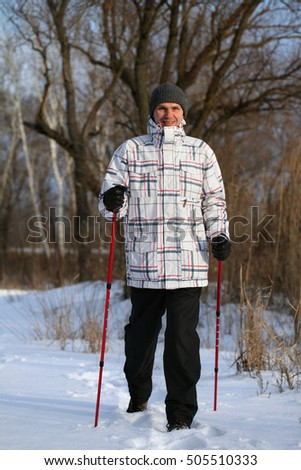 Adult man performing Nordic walking in a snowy winter forest