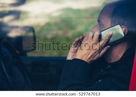 adult man speak on smartphone in car close