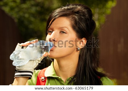adult smiling biker woman on mounting bike drinking mineral water
