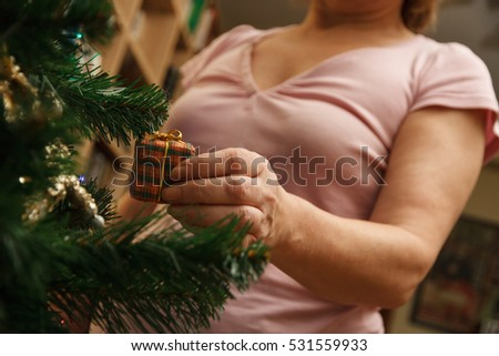 Adult woman decorating the christmas tree with a decoration gift at home.