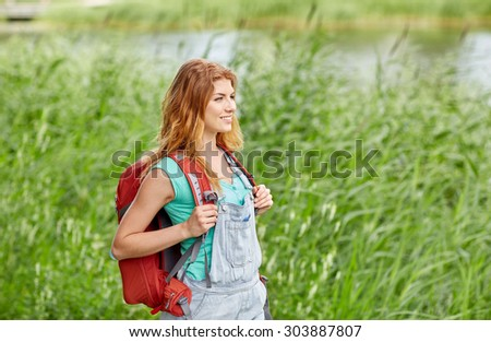 adventure, travel, tourism, hike and people concept - smiling young woman with backpack hiking in woods