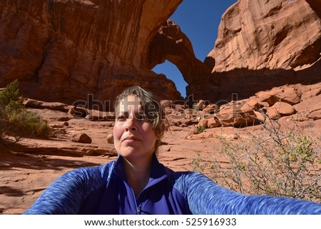 Adventurous Young Woman Hiking at Arches National Park in Utah, USA