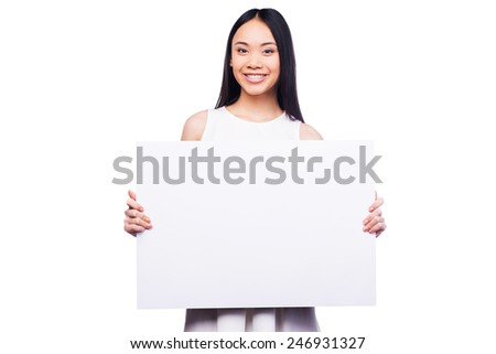 Advertising your product. Beautiful young Asian woman holding copy space and smiling while standing against white background