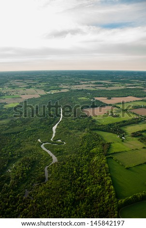 Aerial of a winding river surrounded by forest and agriculture
