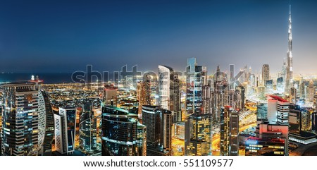 Aerial panoramic view of a big modern city by night. Business bay, Dubai, United Arab Emirates. Colourful nighttime skyline with world's tallest skyscrapers.