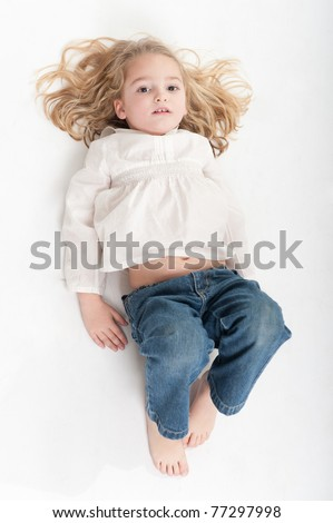 Aerial view of a cute little girl posing on the floor