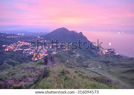 Aerial view of a fishing village by the mountainside on northern coast of Taipei Taiwan ~ Beautiful coastline, coastal highway and a fishing village at dawn with rosy clouds