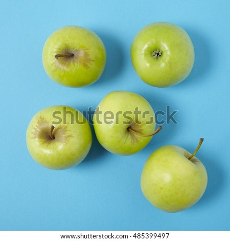 Aerial view of green apples on a bright blue background