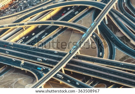 Aerial view of highway road intersection with traffic in Dubai, UAE, at sunset. Famous Sheikh Zayed road in Dubai downtown.