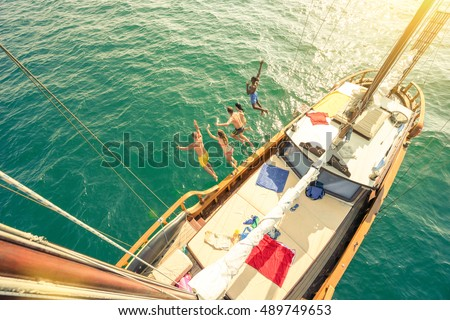 Aerial view of young people jumping from sailing boat on sea trip - Rich happy friends having fun in summer party day - Exclusive vacation concept - Warm vintage filter with enhanced sun flare halos