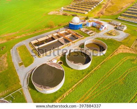 Aerial view to biogas plant from pig farm in green fields. Renewable energy from biomass. Modern agriculture in Czech Republic and European Union.