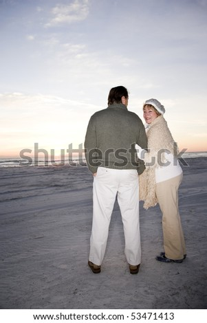 Affectionate senior couple in sweaters on beach at dawn