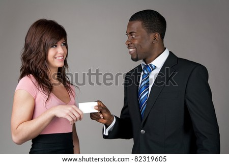 African American businessman giving his business card to a young Caucasian woman.