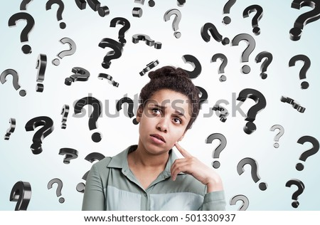 African American girl standing in gray room with floating question marks in the background. Concept of decision making