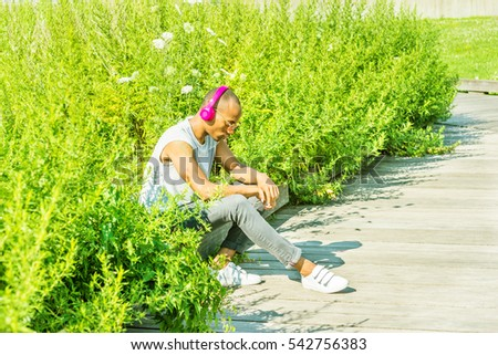 African American Man listening music, wearing gray T shirt, black jeans, white sneakers, sunglasses, pink wireless headphones, sits by tall grasses, looking down, sad, thinking. Color filtered effect