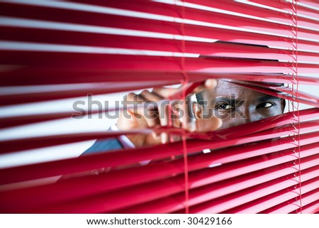 afro-american businessman glancing through red blinds. Copy space